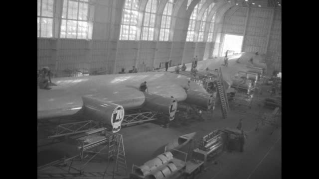 VS both airplane wings in single huge unit filling entire factory floor men moving about on wing and working on it / man on scaffold working on...