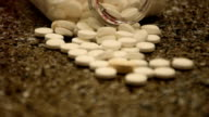 Bottle of Pills spilled all over the Counter white capsules with some random drugs mixed in