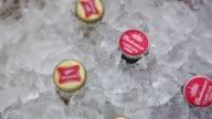 Bottles of AnheuserBusch InBev NV Budweiser brand beer are displayed for a photograph in a cooler alongside SABMiller Miller brand beer in Tiskilwa...