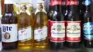 Bottles of AnheuserBusch InBev NV Budweiser brand beer are displayed for a photograph in a refrigerator alongside SABMiller Miller brand beer in...