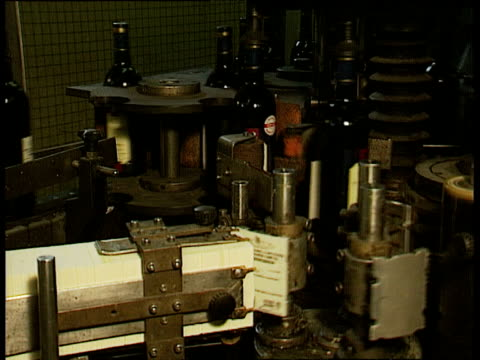 Bottles of red wine are labelled by machinery on production line France