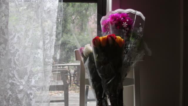 A bouquet of flowers in a window.