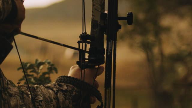 Bogen Jäger zielt darauf ab und nimmt seinen Schuss in Zeitlupe, der Pfeil verlässt den Rest seiner tierische Ziel zu treffen. Diese Aufnahme wurde entwickelt, um bedeuten Erfolg, Fleiß, Ziel macht.