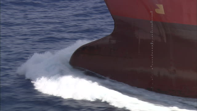 Bow of large boat ploughing through ocean