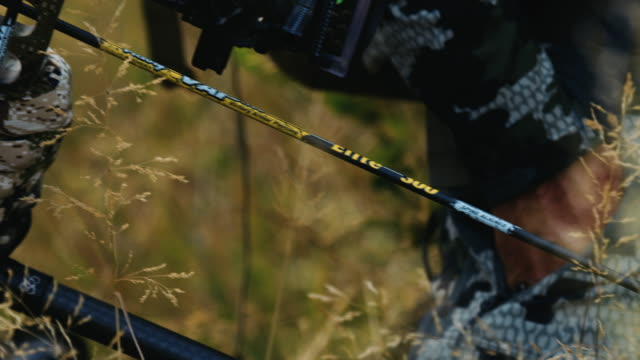 A bowhunter's sharp arrow is clearly visible as he waits and watches his prey move.