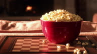 CU Bowl of buttered popcorn on checker board in front of fire
