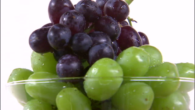 CU ZI Bowl of grapes rotating against white background / Orem, Utah, USA