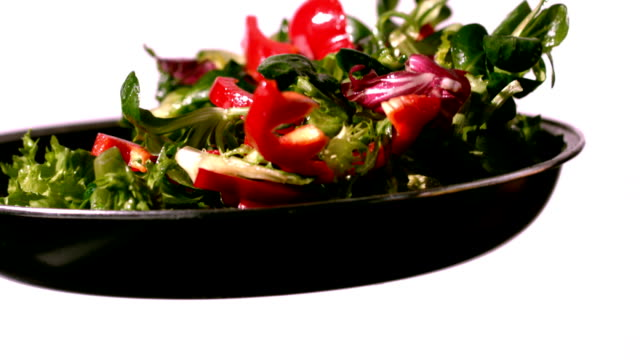 Bowl of salad being tossed