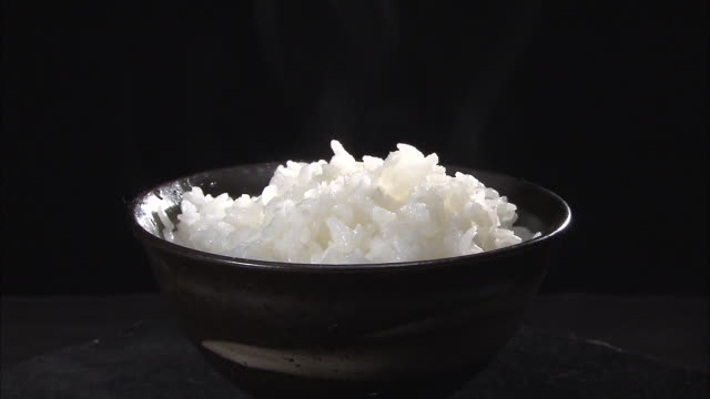 A bowl of steaming, cooked rice rotates on a table.