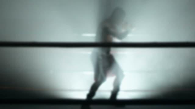 Boxer in spotlight in boxing ring, slow motion