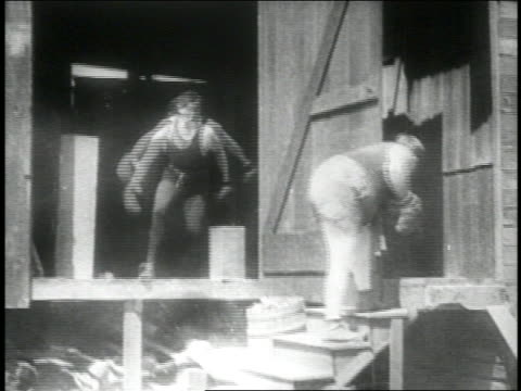 B/W 1914 boxer punching buttocks of 2nd boxer (Fatty Arbuckle) standing on stairs / gun firing