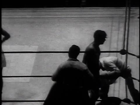 boxer with arm around other boxer / men boxing / boxer knocked down