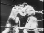 Boxers Al Bazis and Earl Evans dance and punch in ring / boxer falls / referee sends fighter to corner of ring / welldressed spectators watch fight /...