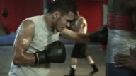 Boxers using heavy bags in gym