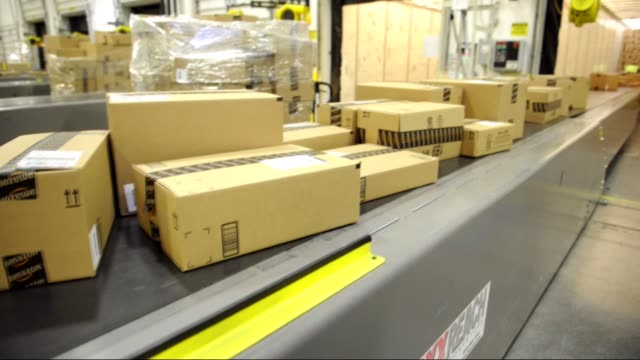 boxes of merchandise on conveyor belt / being loaded onto truck by employees Amazon Boxes Loading onto Truck on November 26 2012 in Phoenix Arizona