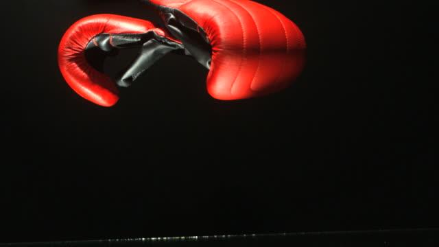 Boxing gloves falling on black background