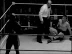Boxing match at the National Sporting Club ENGLAND INT Boxers in centre of ring / Dick Tiger fighting Johnny Read / Referee counting down Tiger /...