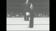 MS boxing ring as announcer introduces German boxer and heavyweight champion Max Schmeling who walks from his corner and bows to spectators / MS...