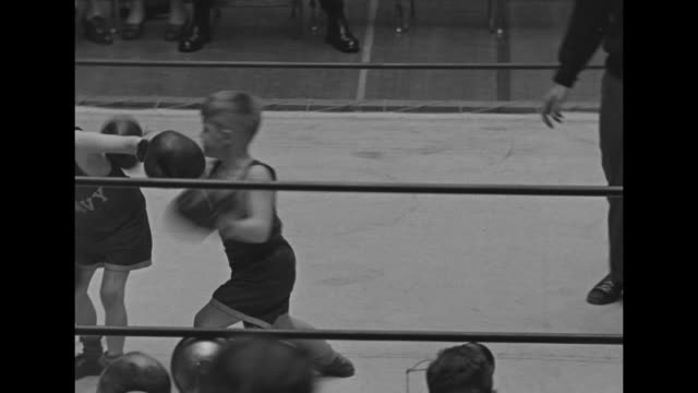 Boxing ring filled with boys of varying ages boxing each other during Navy Junior Boxing Championship matches / VS boxing coach talks to young boys /...