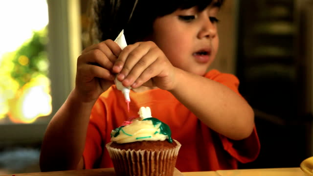 CU Boy (2-3) adding pink frosting on cupcake in kitchen / Los Angeles, California, USA