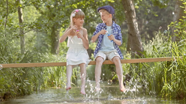 SLO MO TD Boy and a girl sitting on a footbridge blowing bubbles