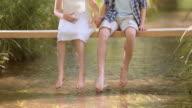 SLO MO jongen en een meisje zittend op een voetgangersbrug opspattend water met hun voeten