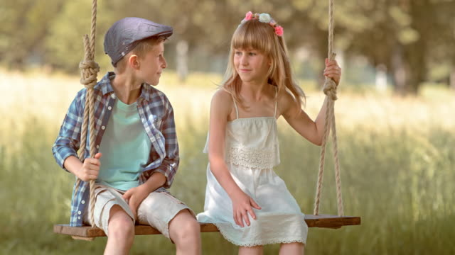 SLO MO Boy and a girl sitting on a swing and smiling