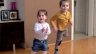 Boy and baby girl dancing and clapping in livingroom