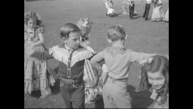 MS boy and girl ages 6 or 7 holds hands as they start to square dance other child couples enter boys wear western shirts and girls wear matching long...