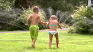 WS ZI MS Boy and girl holding hands and running through sprinkler on lawn / Sherman, CT, USA