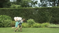 Boy and girl in garden fighting over toy, girl snatches it and runs away