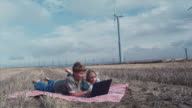 WS Boy and girl looking at laptop in field and wind turbines / Zillah, Washington, USA