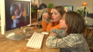 MS, Boy (8-9) and girl (10-11) looking at their picture on computer screen