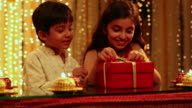 Boy and girl opening a gift box in diwali festival
