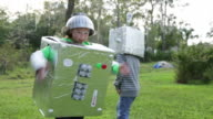 Boy and girl play in robot costumes.