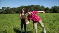 SLO MO MS Boy and girl (8-13) playing with bubble wands in meadow / Hampton, New Jersey, USA