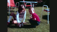 boy and girl playing with guinea pigs cavies in the garden / 1012024