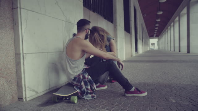 Boy and girl skaters relaxing in urban setting