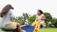 Boy and girl swinging in a Seesaw