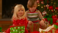MS, Boy (6-7) and girl (2-3) wearing pajamas sitting on floor and opening Christmas present, Richmond, Virginia, USA