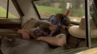 MS, Boy (6-7) and girl (10-11) wearing snorkeling gear sleeping on car back seat, old fashion suitcases in foreground, Tamborine Mountain, Brisbane, Queensland, Australia