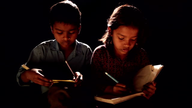 Boy and girl writing on a book