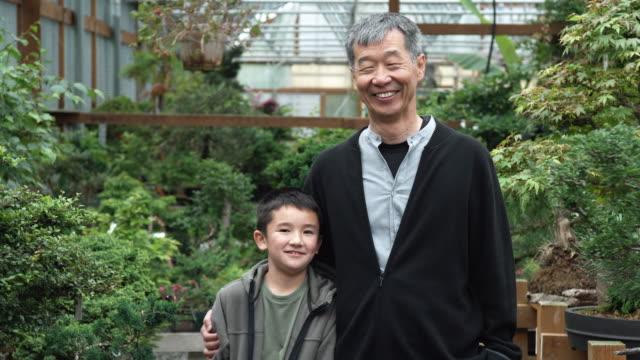 MS Boy and grandfather standing in bonsai nursery / Seattle, Washington, USA