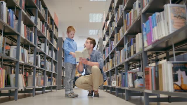 DS A jongen en zijn vader lezen van een boek in de bibliotheek gangpad