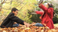 MS Boy (8-9) and sister (12-13) playing with each other in leaves / Montclair, New Jersey, USA