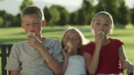 MS Boy (12-13) and two girls (4-11) eating ice cream, sitting on park bench / Orem, Utah, USA