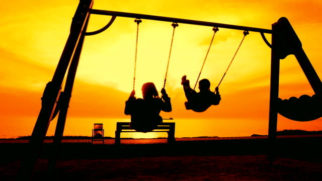 boy and woman on a swing at sunset