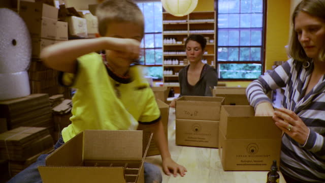 MS Boy and  women packing bottles into boxes / Burlington, Vermont, USA
