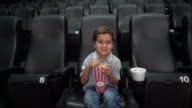 Boy at the cinema watching a movie smiling