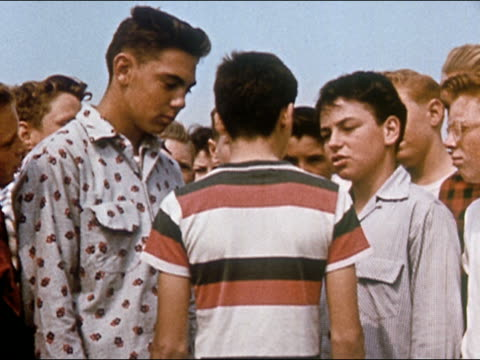 1955 boy being bullied by gang of boys / getting shoved